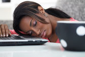 Young women sleeping with her head on a laptop — Stock Photo