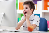 Surprised boy with computer — Stock Photo