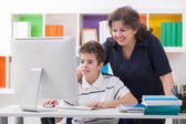 Woman using computer with son — Stock Photo
