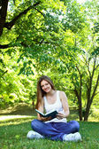Young woman in green park, book and reading — Stock Photo