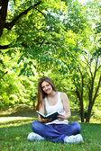 Jeune femme dans le parc verdoyant, livre et lecture — Photo