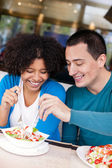 Young couple sharing salad — Stock Photo