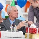 Senior man celebrating his birthday with family — Stock Photo #28284481