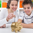 Siblings with piggybank — Stock Photo