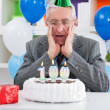 Surprised senior man looking at birthday cake — Stock Photo