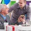 Smiling senior man receiving gift for birthday — Stock Photo