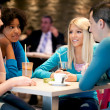 Group of teenagers in a cafe enjoy  — Stock Photo