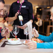 Nice dinner in a restaurant - waiter offers wine — Stock Photo