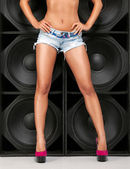 Sexy legs over wall of speakers — Stock Photo