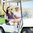 Couple in golf buggy — Stock Photo