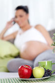 Pregnant woman with fruit on table — Stock Photo