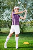 Girl golfer hitting the ball — Stock Photo