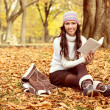 Woman sitting on the autumn leaves and reading book — Stock Photo