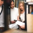 Students reading book in library — Stock Photo #30403795