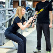 Stock Photo: Woman working out, her personal trainer helping her