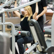 Woman with her personal fitness trainer in the gym — Stock Photo