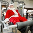 Stock Photo: Father Christmas doing exercises in gym
