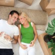 Couple lying on floor in new home — Stock Photo