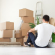 Couple sitting in room full of moving boxes — Stock Photo #31883749