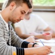 Male college student sitting in a classroom — Stock Photo