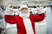 Santa Claus doing exercise at gym — Stock Photo