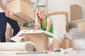 Happy woman unpacking in new home — Stock Photo