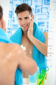 Young man applying aftershave — Stock Photo