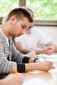 男子大学生は教室に座っています。 — ストック写真