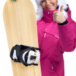 Woman with snowboard giving thumbs up — Stock Photo #32744219