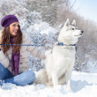 Young woman with her dog in snow — Stock Photo