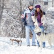 Couple with dog in snowy forest  — Stock Photo