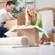 Young couple unpacking or packing boxes — Stock Photo
