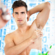 Постер, плакат: Man applying antiperspirant