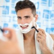 Happy laughing man shaving his face — Stock Photo #32748237