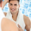 Reflection of young man in mirror — Stock Photo