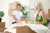 Excited couple in new home unpacking boxes — Stock Photo