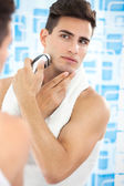 Young guy shaving his beard off with an electric shaver — Stock Photo