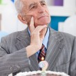 Thinking senior man with birthday cake — Stock Photo