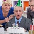 Family together blowing in the candles — Stock Photo