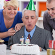 Family together blowing in the candles — Stock Photo #35598207