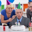 Senior man blowing in the candles on cake — Stock Photo
