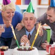 Senior man blowing candles — Stok fotoğraf