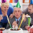 Foto Stock: Senior man blowing candles