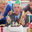 Senior man blowing candles — Stockfoto
