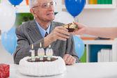 Smiling senior man receiving birthday gift — Stock Photo