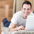 Happy man using laptop in his new home — Stock Photo