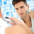 Man shaving beard with electric shaver — Stock Photo #35600551