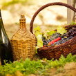 Bottle of wine and grapes in basket — Stockfoto