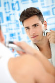 Man shaving beard with electric shaver — Stock Photo