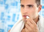 Man applying balsam for lips — Stock Photo